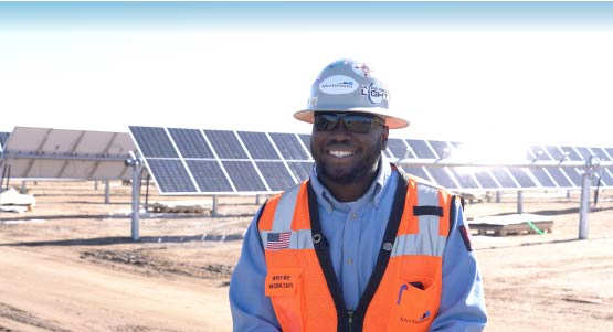 Smiling photo of Sheldon Lincoln, Electrical Superintendent at Mortenson in an orange vest in front of a field of solar panels.